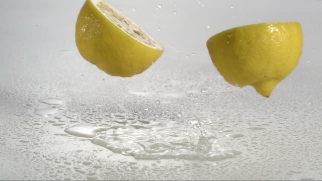 vídeos de stock e filmes b-roll de lemon falling and creating splashing droplets - limão