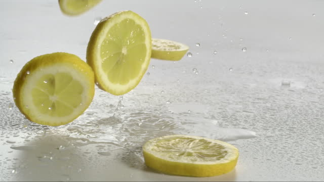 stockvideo's en b-roll-footage met lemon falling and creating splashing droplets - vijf dingen