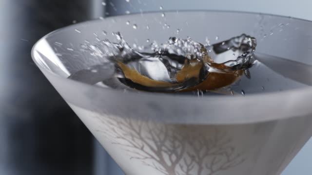 stockvideo's en b-roll-footage met lemon falling in to martini glass - martiniglas