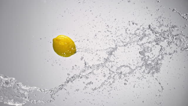 slo mo lemon flying into a water splash in the air - lemon stock videos & royalty-free footage
