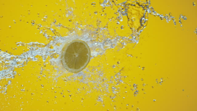 slo mo lemon half colliding with water on yellow background - citrus fruit stock videos and b-roll footage