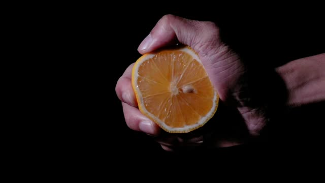 lemon in super slow motion being squeezed on black background - citrus fruit stock videos and b-roll footage