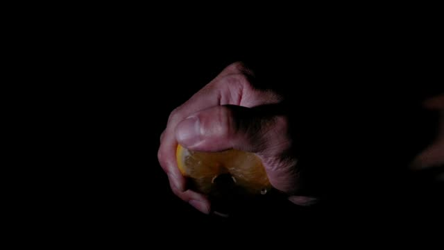 Lemon in super slow motion being squeezed on black background