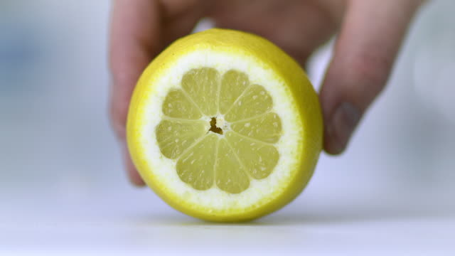 A lemon placed on a white chopping board being held by hand and sliced very finely