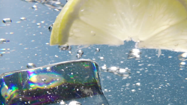 lemon slice and ice cube falling down in water - lemon stock videos & royalty-free footage