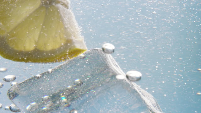 lemon slice falling down in water with ice cube - freshness stock videos & royalty-free footage