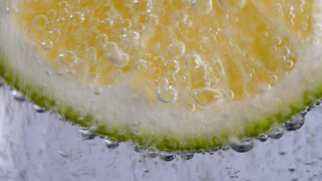 stockvideo's en b-roll-footage met citroen schijfje in bruisend water - verfrissing