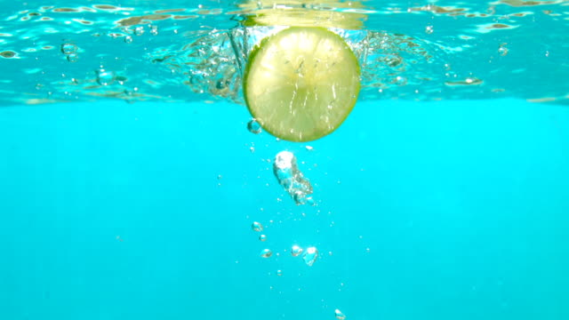 lemon slice is falling in blue water with bubbles in slow motion underwater shot tabletop - lime stock videos & royalty-free footage