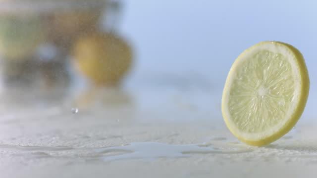 Lemon slice rolls through mist on wet, white surface