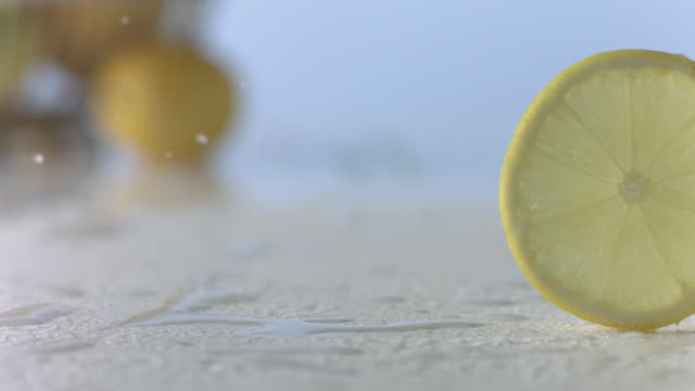 lemon slice rolls through water on white surface - lemon stock videos & royalty-free footage