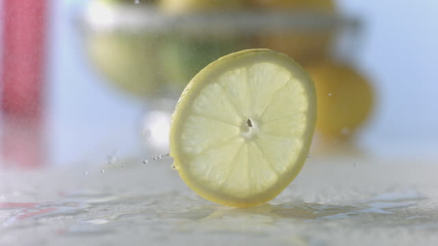 lemon slice twirls in the mist on wet, white surface - inquadratura dall'alto di un tavolo video stock e b–roll