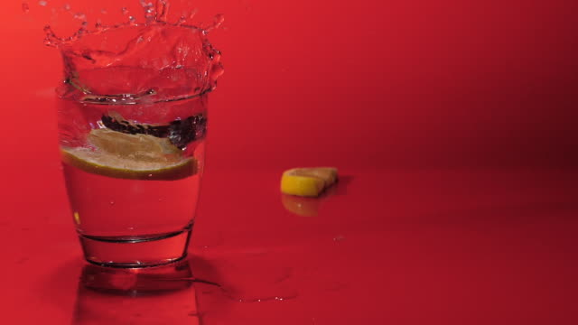 lemon slices fall down in glass with soda,gin,water - real time - cachaça stock videos & royalty-free footage