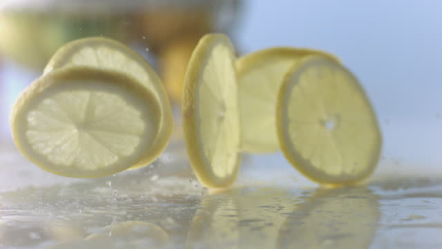Lemon slices fall to wet, white surface