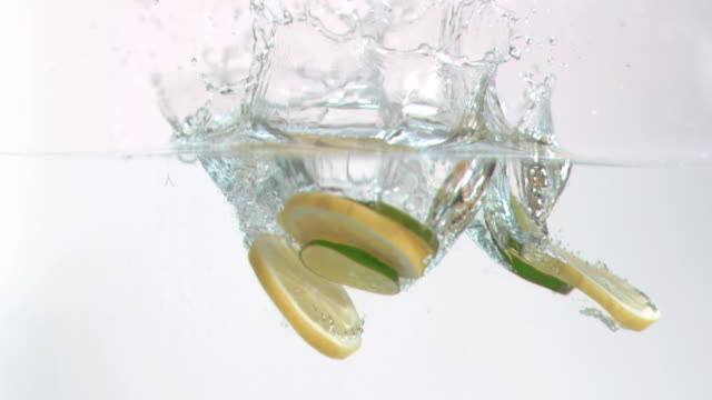 Lemon slices falling into water in super slow motion