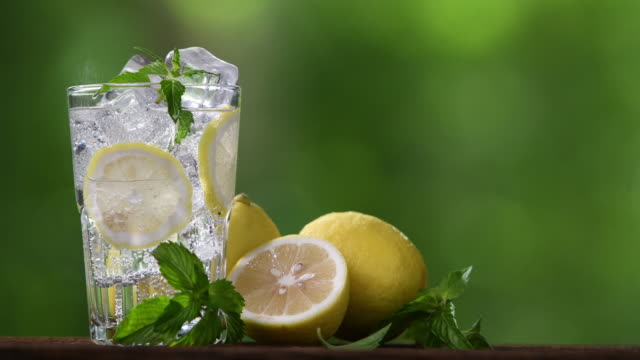lemon soda with sliced lemon in glass - detox stock videos & royalty-free footage