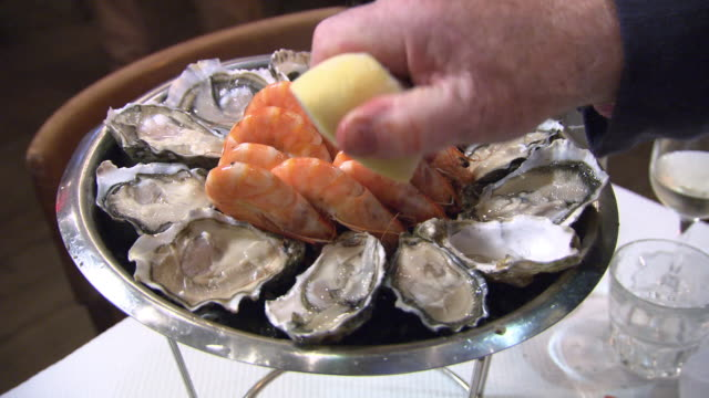 cu lemon squeezed over tray of seafood - shrimp seafood stock videos & royalty-free footage
