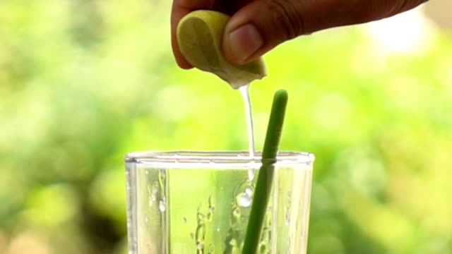 lemon squeezing into glass of water,slow motion - lemon stock videos & royalty-free footage