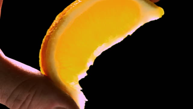 cu lemon wedge holding by two finger pinch being squeezed and juice squirting out / los angeles, california, united states - loopable moving image stock videos & royalty-free footage