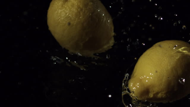 Lemons double spin falling into water, black background