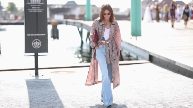 vídeos de stock e filmes b-roll de lena lademann wearing flared denim jeans cropped top belted coat seen outside munthe during the copenhagen fashion week spring/summer 2019 on august... - copenhaga