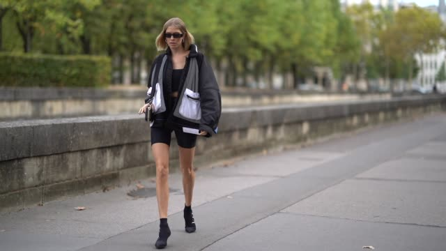 lena perminova wears a black and white jacket, black short leggings, black shoes sunglasses, outside valentino, during paris fashion week womenswear... - valentino designer label stock videos & royalty-free footage