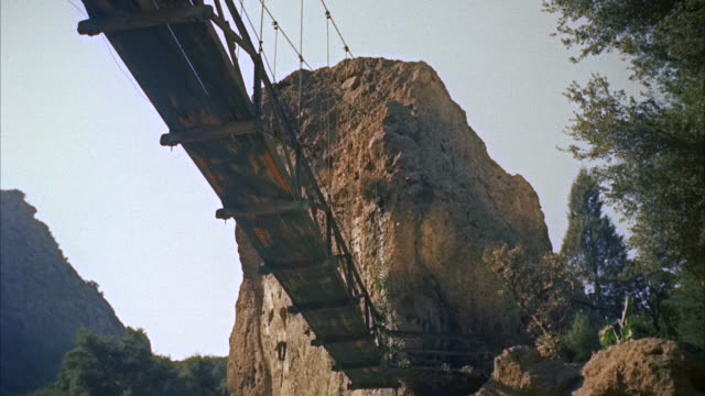 vídeos de stock e filmes b-roll de ws pov  length of suspension bridge over  deep gorge and  man appears on  - ponte suspensa