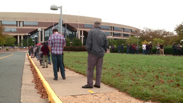 lengthy lines snake outside fairfax government center as early votes are caste for 2020 us election - fare la fila video stock e b–roll