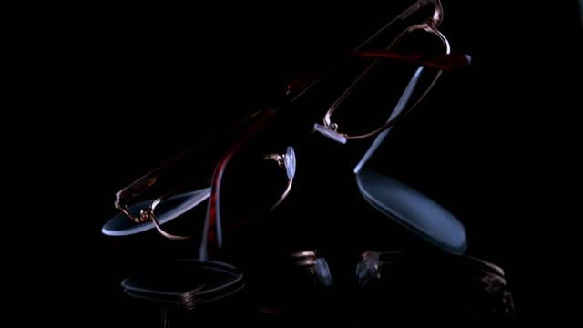vídeos y material grabado en eventos de stock de slo mo ld una lente que se cae de las gafas graduadas cuando golpean la superficie negra - lente
