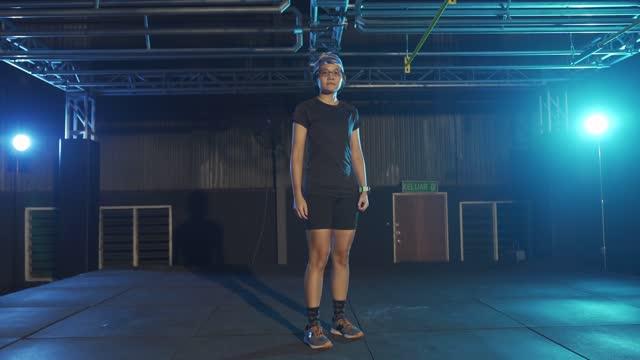vidéos et rushes de lentille flare retour éclairé asiatique chinois instructeur de remise en forme avec portrait foulard regardant l'appareil photo avec une attitude cool - cadrage en pied