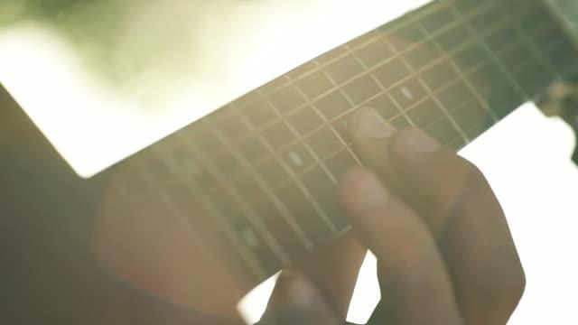 vídeos de stock, filmes e b-roll de lens flare guitar - violão acústico