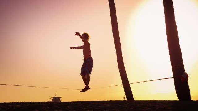 Lens flare shot of a man balancing on the slackline near Venice Beach, California