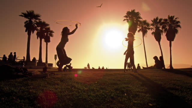 lens flare shot of people strolling near venice beach, california filmed in slow motion - venice beach stock videos & royalty-free footage