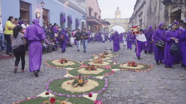 lent / easter catholic celebration at antigua guatemala. multicoloured flower carpets on the cobblestone street. people dressed in purple costume crossing santa catalina arch. - guatemala stock videos & royalty-free footage