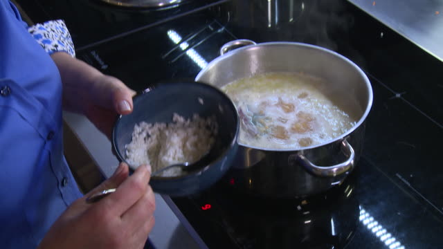 lentil soup. view of a woman's hands adding rice over lentils and onions in a pot to thicken a soup. - cooking pan stock videos & royalty-free footage