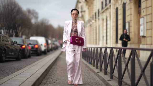 leonie hanne wears a black headband, earrings, a colorful top, a pale pink pantsuit with wide-leg pants, a raspberry-red bag, outside y/project,... - street style stock videos & royalty-free footage