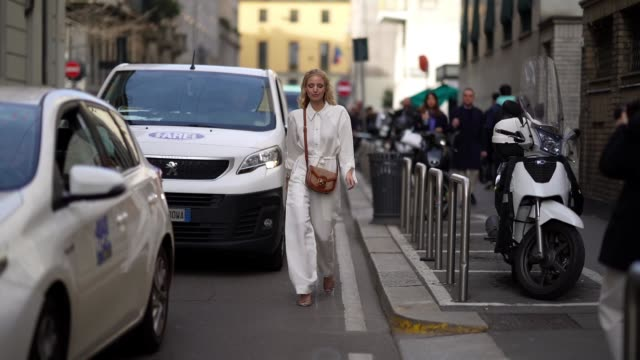 leonie hanne wears a brown bag, a white shirt, white flared pants, bracelets, outside etro, during milan fashion week fall/winter 2020-2021 on... - street style stock videos & royalty-free footage