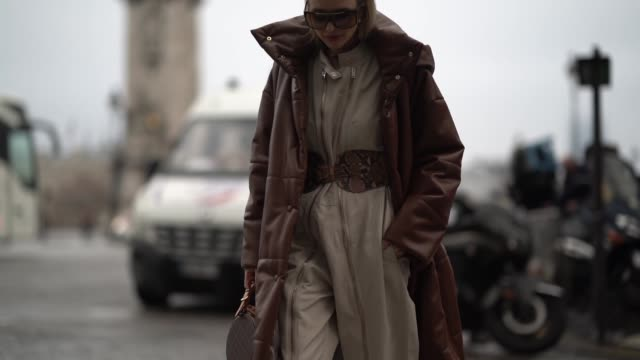 leonie hanne wears a brown long puffer coat a vuitton bag a white jumpsuit a snake print large belt snake print boots outside alexandre vauthier... - spring summer collection stock videos & royalty-free footage