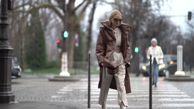 leonie hanne wears a brown long puffer coat a vuitton bag a white jumpsuit a snake print large belt snake print boots outside alexandre vauthier... - jumpsuit stock videos & royalty-free footage