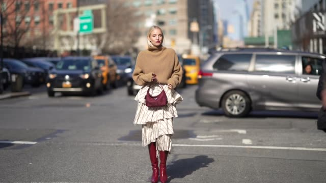 leonie hanne wears a brown turtleneck wool oversized pullover, a purple prada bag, a ruffled skirt, burgundy leather high pointy boots, outside brock... - jumper stock videos & royalty-free footage