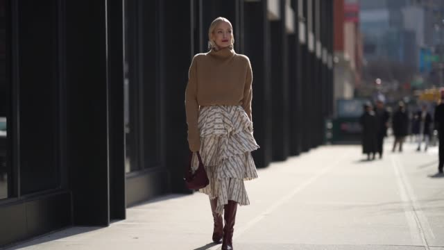 leonie hanne wears a brown turtleneck wool oversized pullover a purple prada bag a ruffled skirt burgundy leather high pointy boots outside brock... - pullover stock-videos und b-roll-filmmaterial