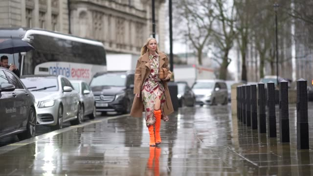 leonie hanne wears a colored floral print dress a brown trench coat a brown bottega veneta quilted bag orange high heeled boots during london fashion... - floral pattern stock videos & royalty-free footage