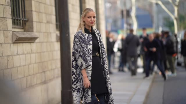 stockvideo's en b-roll-footage met leonie hanne wears a dior saddle bag blue denim flared jeans pants a wax printed coat pointy shoes a dior choker outside dior during paris fashion... - gepunt