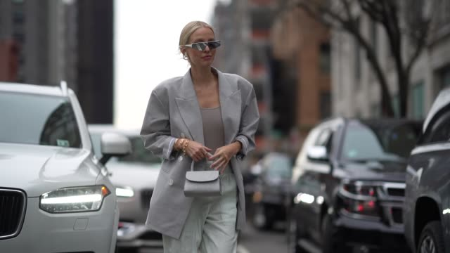 leonie hanne wears a gray oversized blazer jacket, a mini bag, pale green flowing pants, pointy shoes, a low neck gray top, during new york fashion... - gray jacket stock videos & royalty-free footage