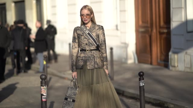 Leonie Hanne wears a green khaki lace dress a Dior bag a jacket with printed features outside Dior during Paris Fashion Week Haute Couture Spring...