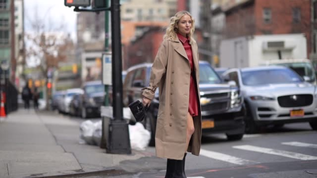 leonie hanne wears a light brown trench coat a red leather dress, black leather boots, a bag, outside longchamp, during new york fashion week... - トレンチコート点の映像素材/bロール