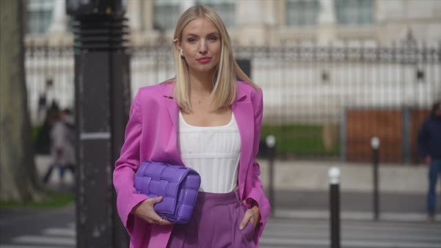 leonie hanne wears a neon pink oversized blazer jacket, a white low neck top, a purple bottega veneta quilted bag, purple flared pants, white shoes,... - ストリートスナップ点の映像素材/bロール