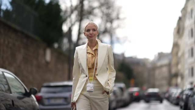 vidéos et rushes de leonie hanne wears a pale orange shirt, a yellow mini bag from jacquemus, a white mini bag from jacquemus, a white blazer jacket, cropped pants,... - fashion show