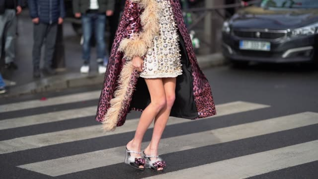 stockvideo's en b-roll-footage met leonie hanne wears a silver shiny dress with attached pearls a purple leopard print coat shoes with white faux fur a black bag outside miu miu during... - modeweek