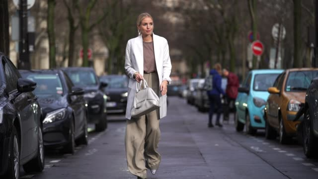 leonie hanne wears earrings a bangle watch a light brown top a white jacket a creamcolor bag sandcolor widelegs fulllength pants glittering pointy... - full length stock videos & royalty-free footage