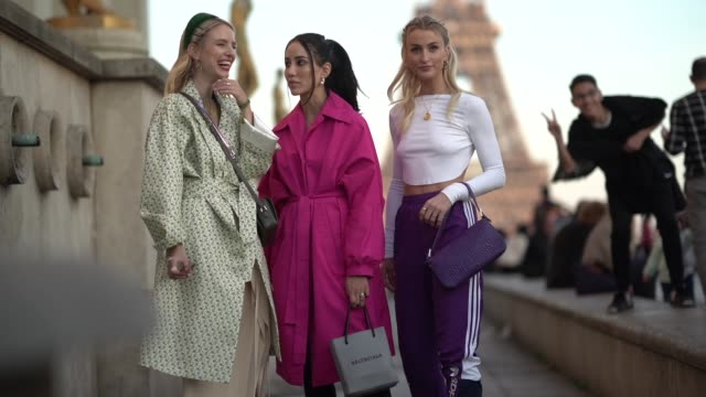 leonie hanne wears earrings, a green hairband, hairpins, a camel gathered top, a green floral print trench coat, a brown handbag, a beige skirt,... - street style stock videos & royalty-free footage